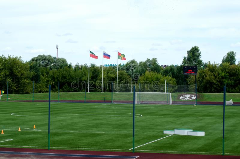 Soccer field with the flags of Russia and Tatarstan. Green soccer field with the flags of Russia and Tatarstan in cloudy weather under the open sky summer stock photography