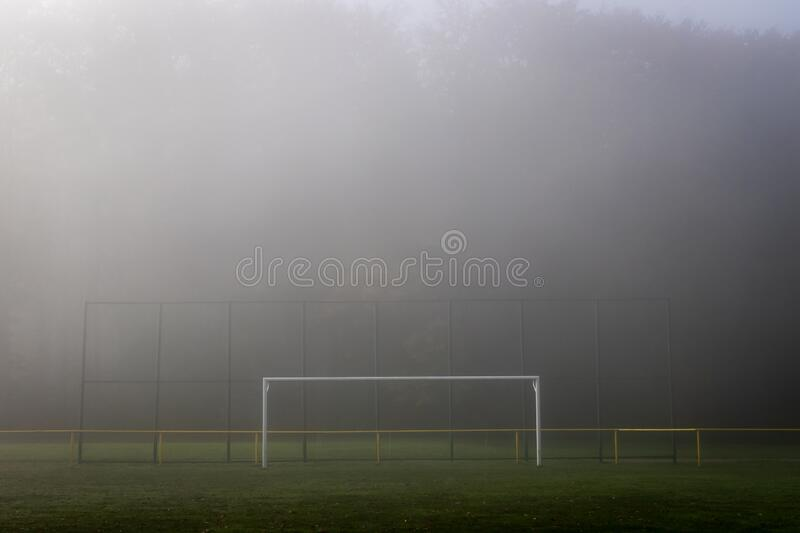 Soccer field and soccer goal in mist stock image