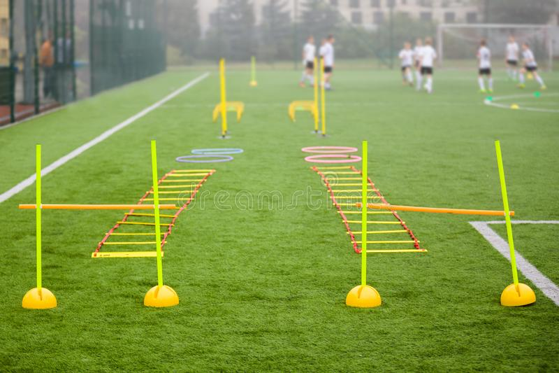Soccer field with training equipment and fence in background. Junior football team training with coach in the background. Soccer football training session for royalty free stock photos