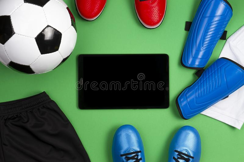 Soccer football background. Tablet computer with soccer ball, blue boots, cleats, white t-shirt and black shorts on. Green background. Flat lay, top view royalty free stock photography