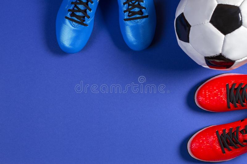 Soccer football background. Top view of soccer ball and two pair of soccer football sports shoes on blue background.  royalty free stock images