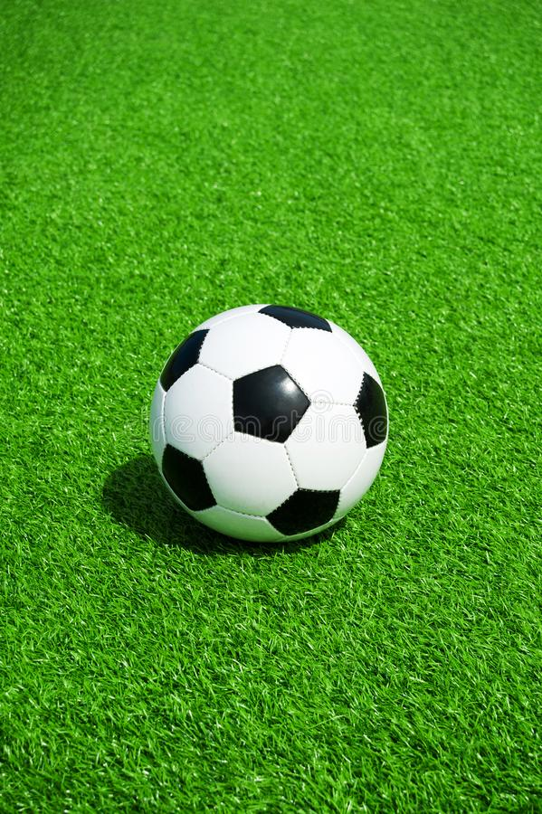 Soccer, football, ball, classic black and white on clean green field, space for text, good for banner. Soccer ball black and white on green artificial turf stock images