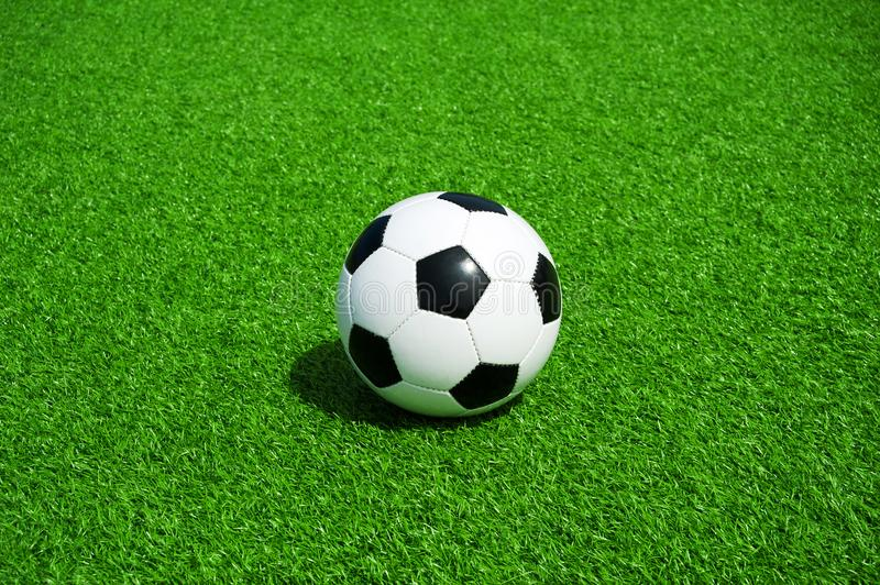 Soccer, football, ball, classic black and white on clean green field, space for text, good for banner. Soccer ball black and white on green artificial turf stock image