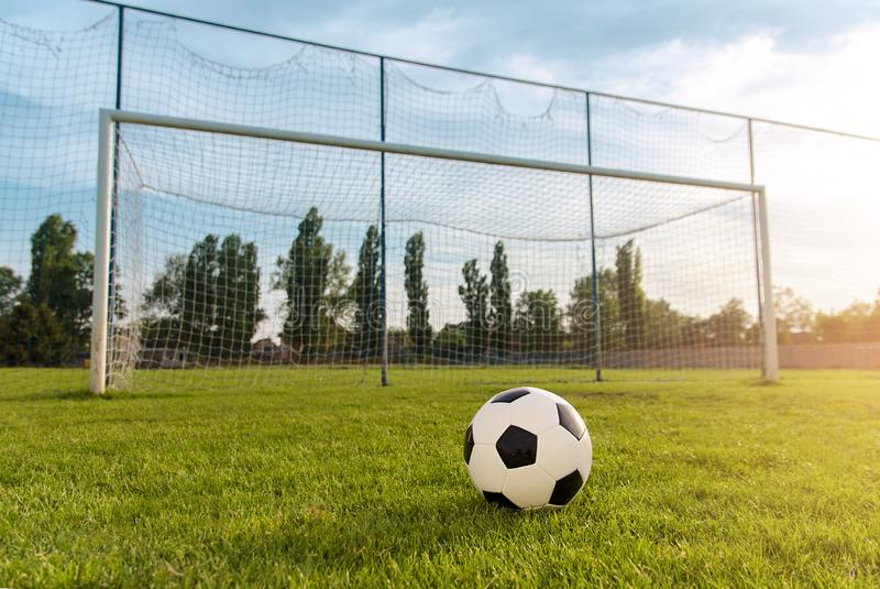 Soccer/football ball in front of empty goal at sunset royalty free stock photography
