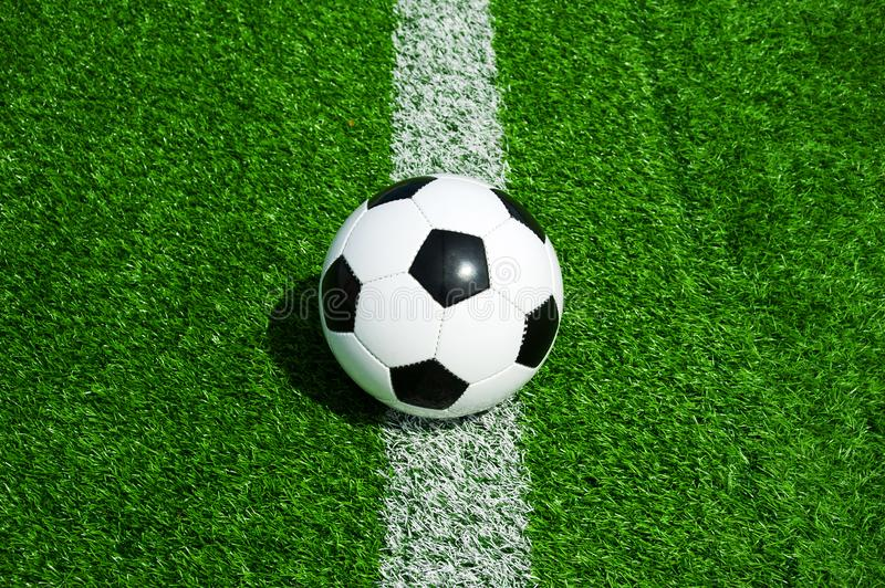 Soccer, football, ball, on line, white mark, classic black and white on clean green field, space for text, good for banner. Soccer ball black and white on green royalty free stock photography