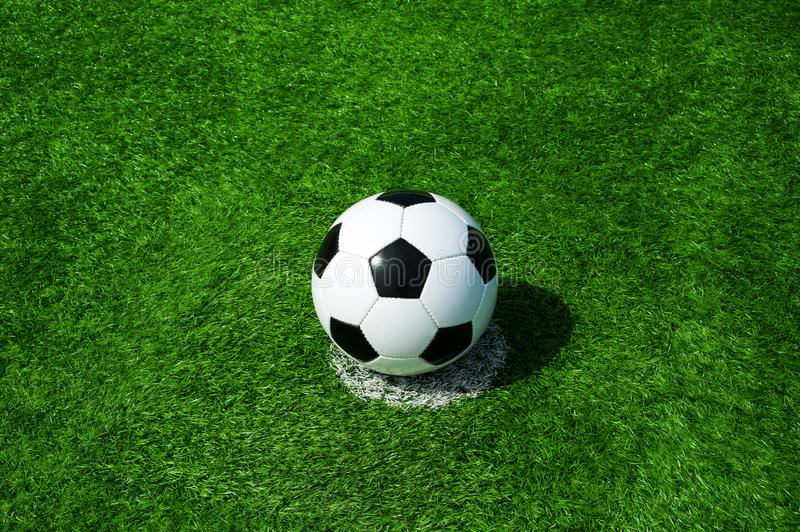 Soccer, football, ball, on penalty spot, classic black and white on clean green field, space for text, good for banner. Soccer ball black and white on green stock photos