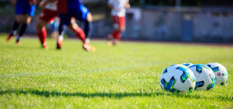 Soccer football balls on the soccer field. Soccer football balls on the green field stock photo