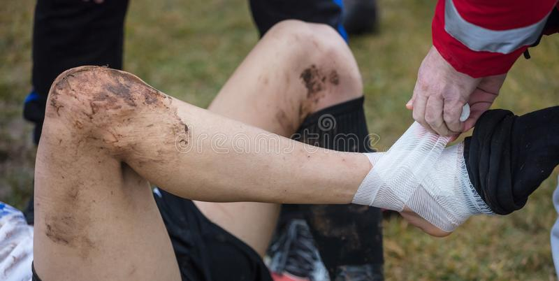 Soccer, football concept. Injured footballer lay down on field with hurting ankle. Blurred background, close up view. royalty free stock photo