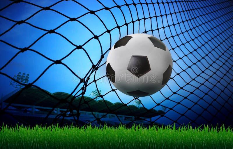 Soccer football in goal net and stadium blue sky b