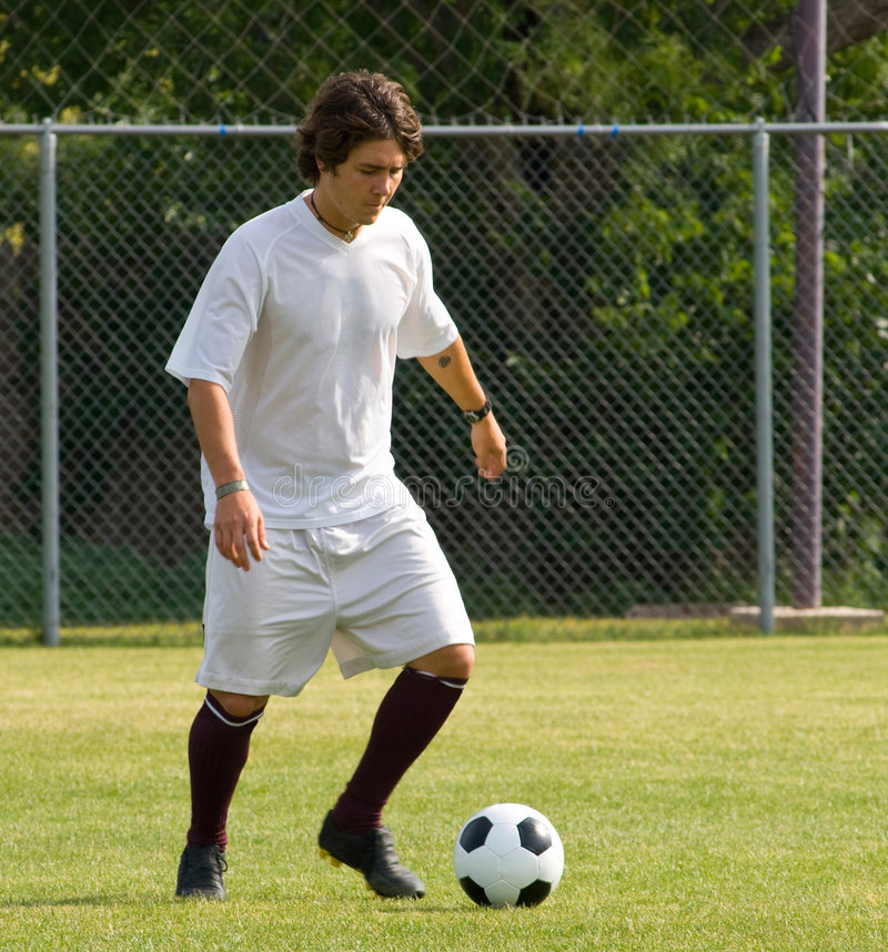 Soccer - Football Player Dribbling. Soccer or bootball player in white dribbling soccer ball royalty free stock photos
