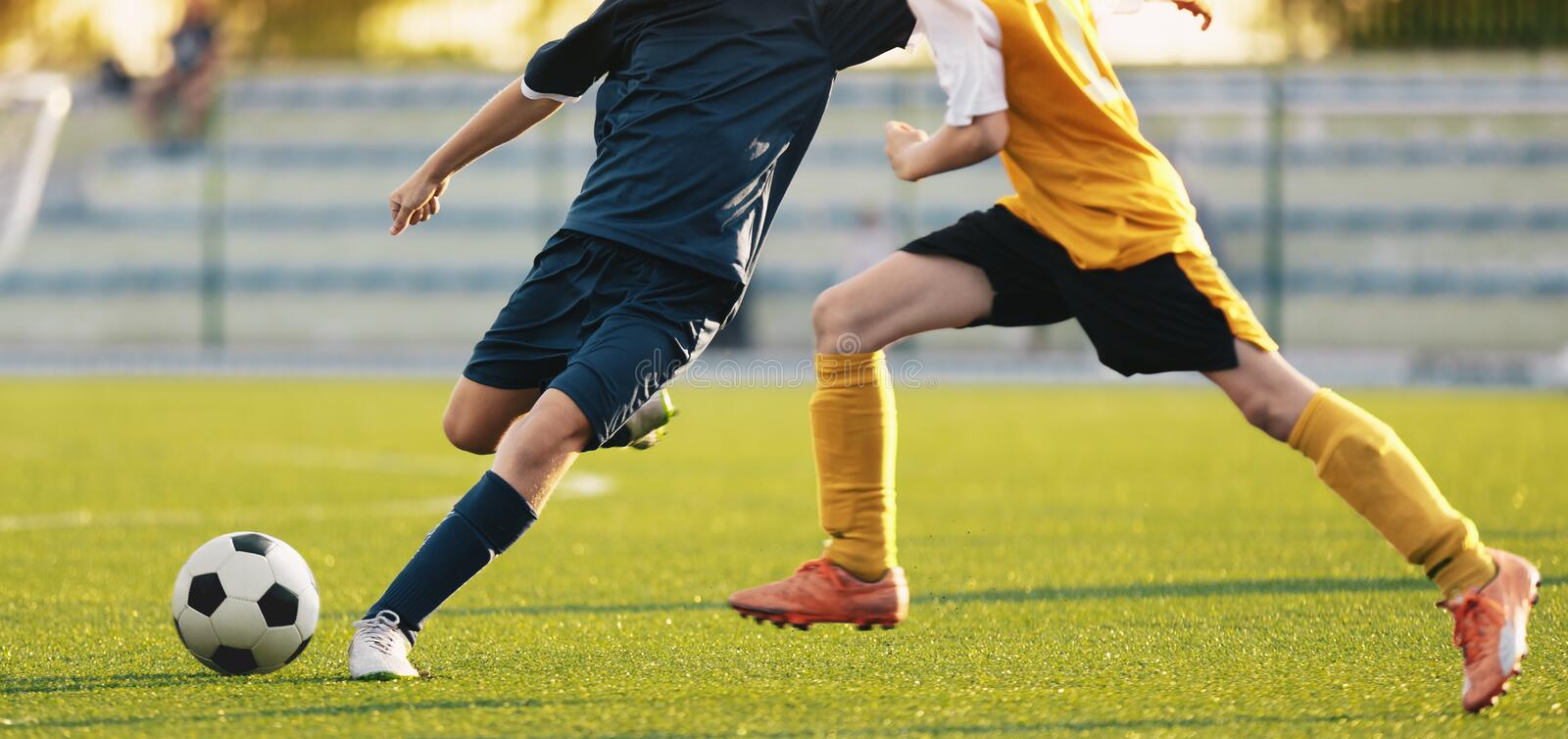 Soccer Football Players Compete at the Stadium. Two Footballers Running and Kicking Soccer Ball. Football Match Background. Football Tournament Game for Youth stock images