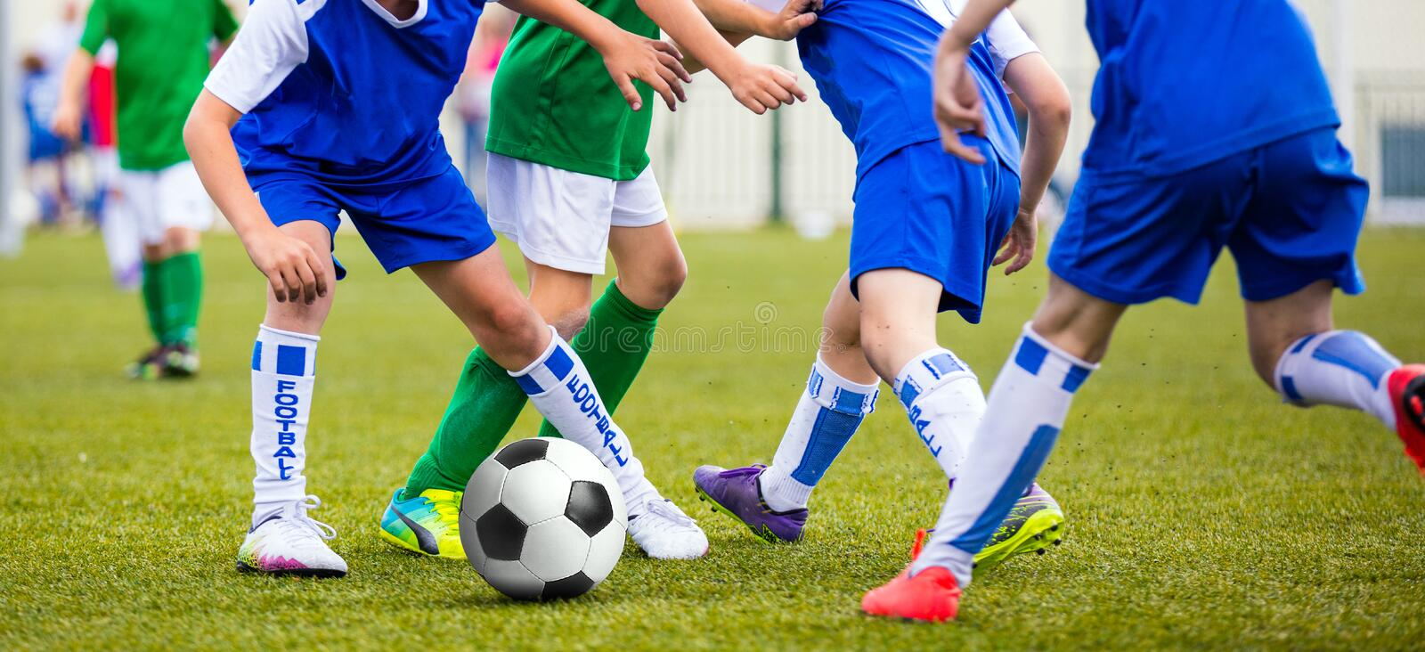 Soccer game for kids. Children kicking football ball. Boys in blue and green soccer shirts playing football tournament on sports field royalty free stock images