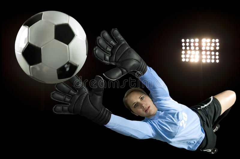 Soccer Goalie. Blocks ball in stadium royalty free stock image