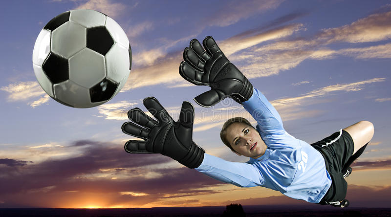 Soccer Goalie. Blocks ball in sunset. Horizontal shot stock photo