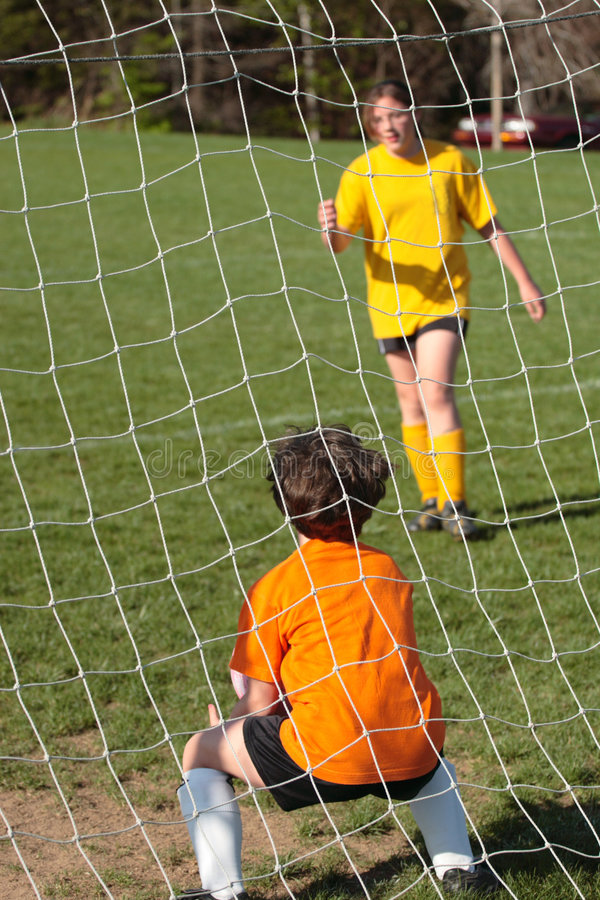 Soccer Goalie. Girl kicking ball at soccer field practice in goalie pen stock photo