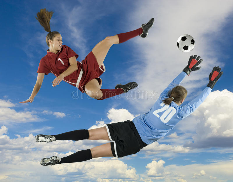 Soccer Kicker and Goalie. Soccer player kicks ball towards goal, while goalie blocks royalty free stock images