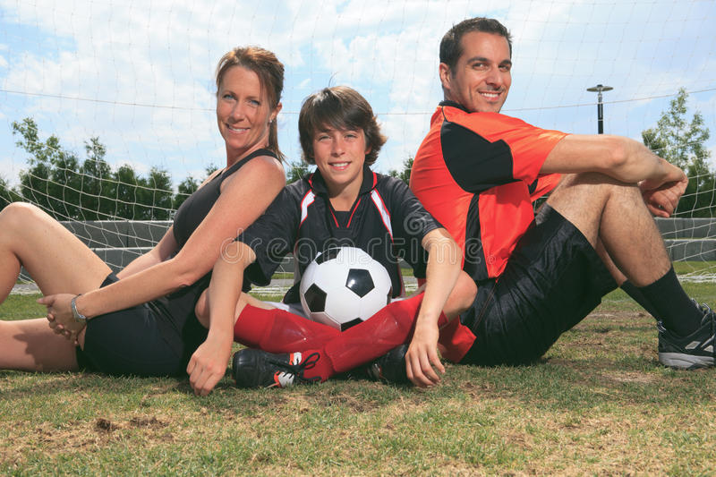 Soccer kid. A soccer family portrait sitting on the ground with the ball stock images