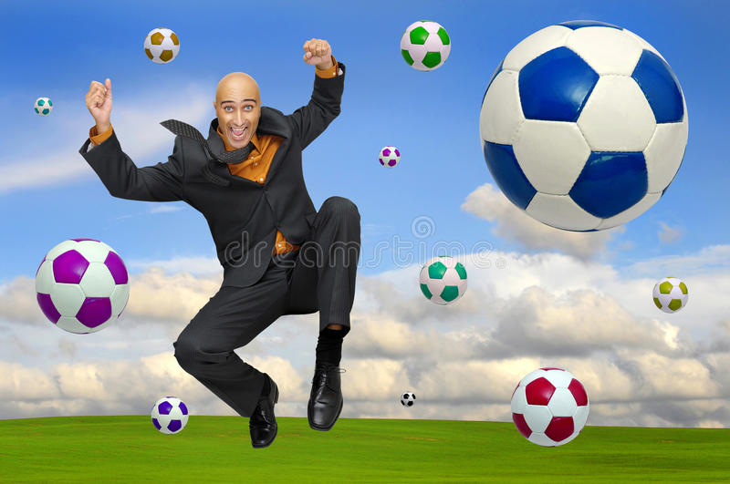 Soccer party. Businessman playing soccer outdoors in a green field royalty free stock image