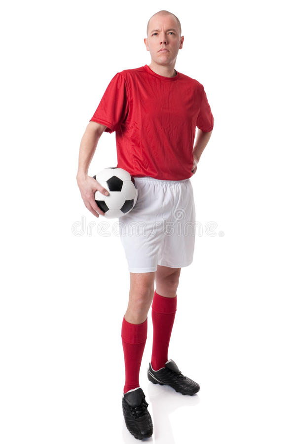 Soccer player. Full isolated studio picture from a young soccer player with ball stock image