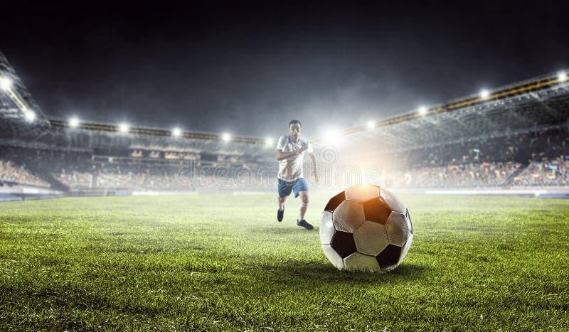 Soccer player in action. Mixed media. Soccer player at stadium kicking ball. Mixed media royalty free stock photography