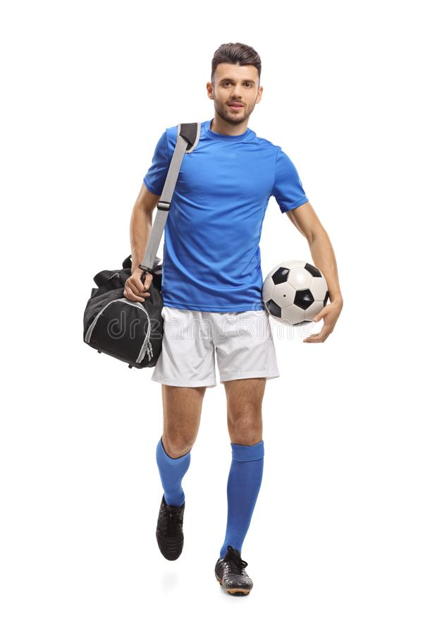 Soccer player with a bag and a football walking towards the came stock photos