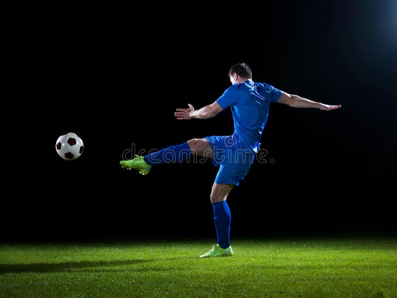 Soccer player. Doing kick with ball on football stadium field isolated on black background royalty free stock photo