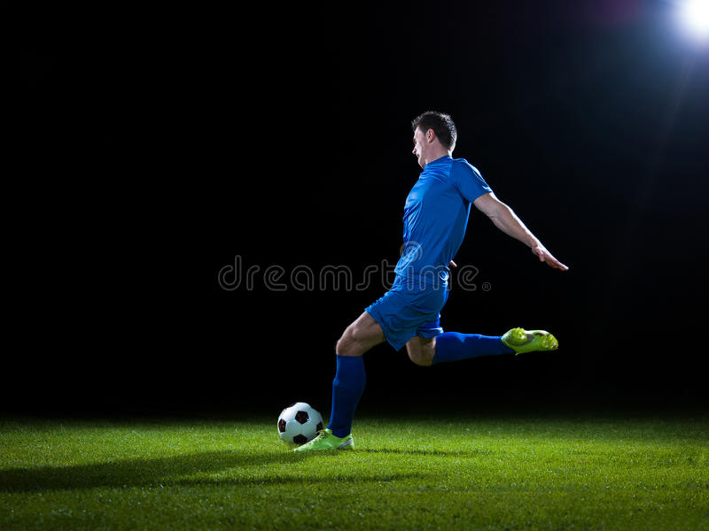 Soccer player. Doing kick with ball on football stadium field isolated on black background royalty free stock image