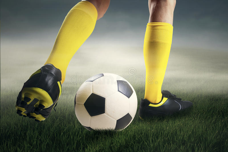 Soccer player dribbling the ball at field. Closeup of soccer player dribbling the ball at field royalty free stock photo