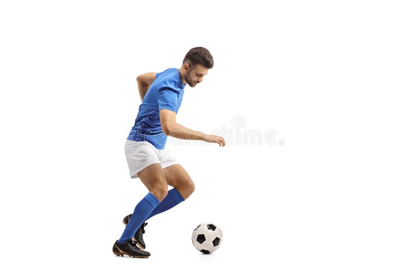Soccer player dribbling. Full length profile shot of a soccer player dribbling isolated on white background stock photography