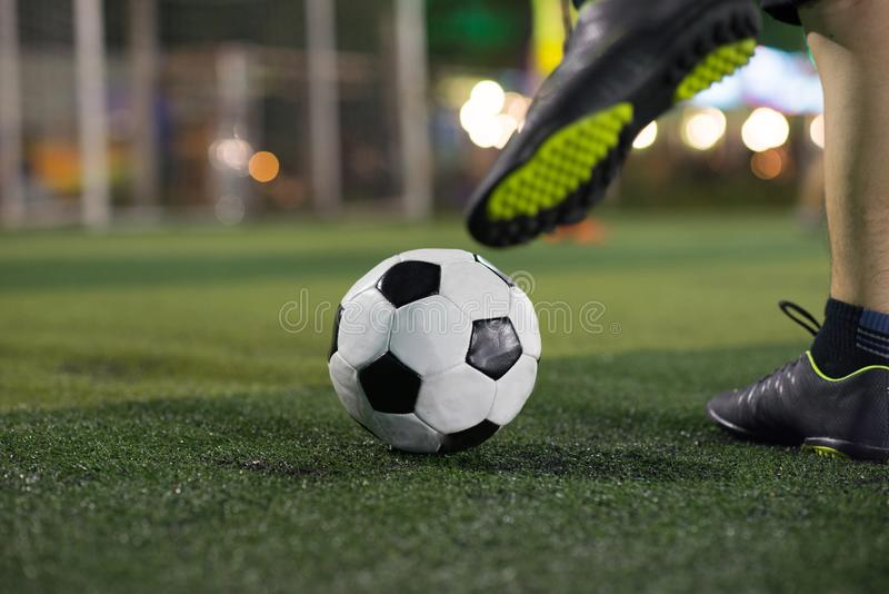 Soccer player foot kicking ball on football field royalty free stock images