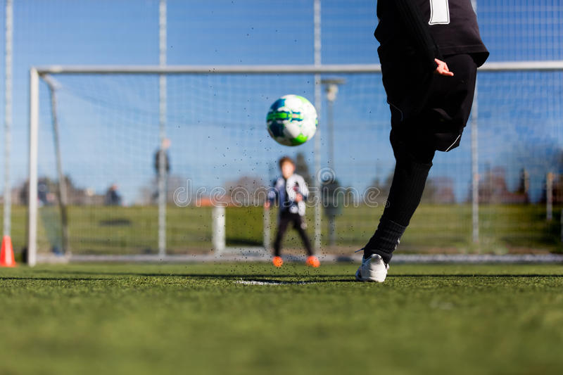 Soccer player and goalie during penalty shootout. Close-up of young soccer player taking a penalty kick against a young blurred boy acting as goalie in the goal royalty free stock photography