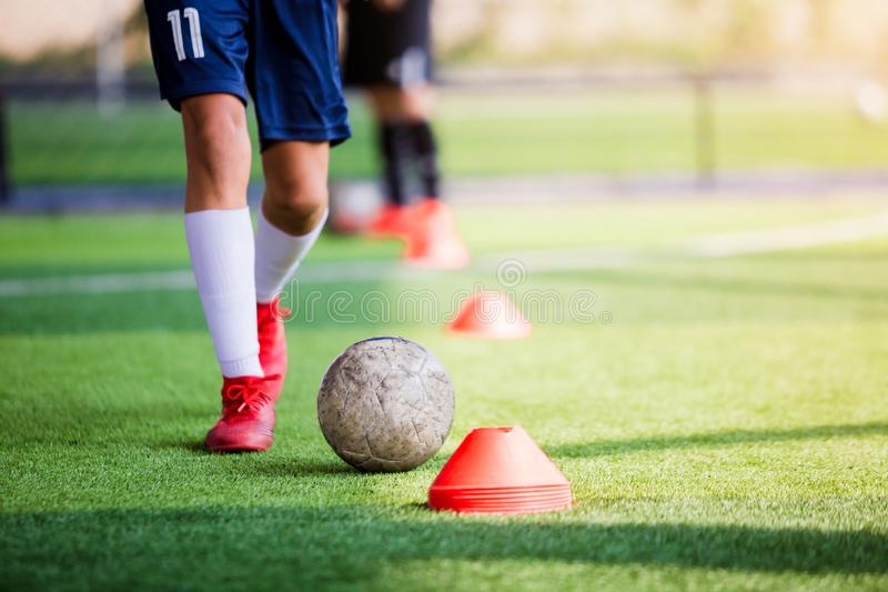 Soccer player jogging and control ball between cone markers for soccer training. Football academy. kid soccer players are training royalty free stock photography