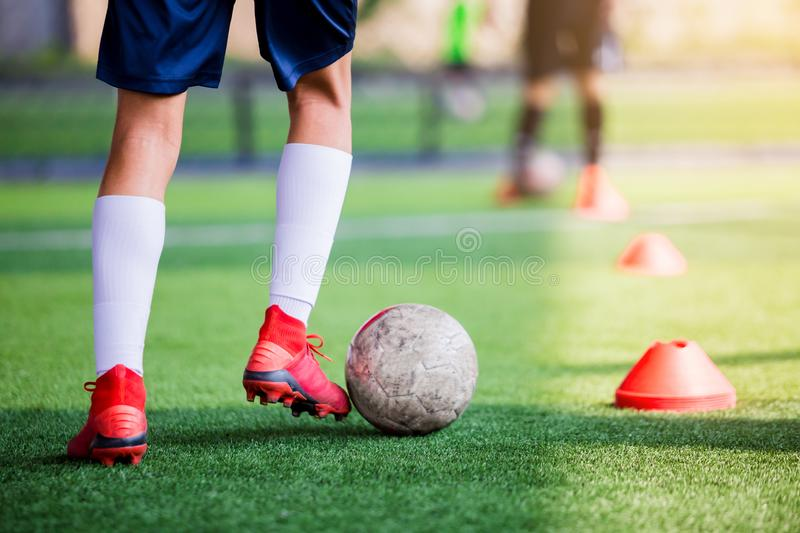 Soccer player jogging and control ball between cone markers for soccer training. Football academy. kid soccer players are training stock image