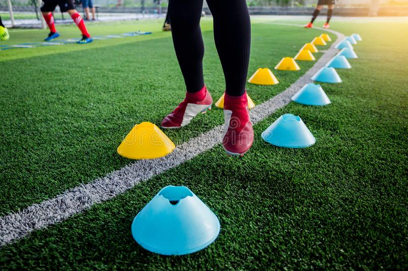 Soccer player Jogging and jump between cone markers on green art. Ificial turf for soccer training. Football or Soccer Academy royalty free stock photos