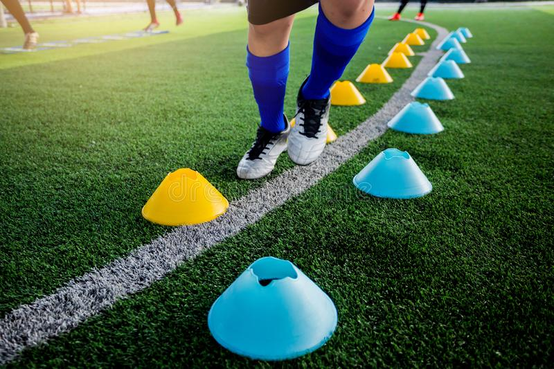Soccer player Jogging and jump between cone markers on green art. Ificial turf for soccer training. Football or Soccer Academy stock photo