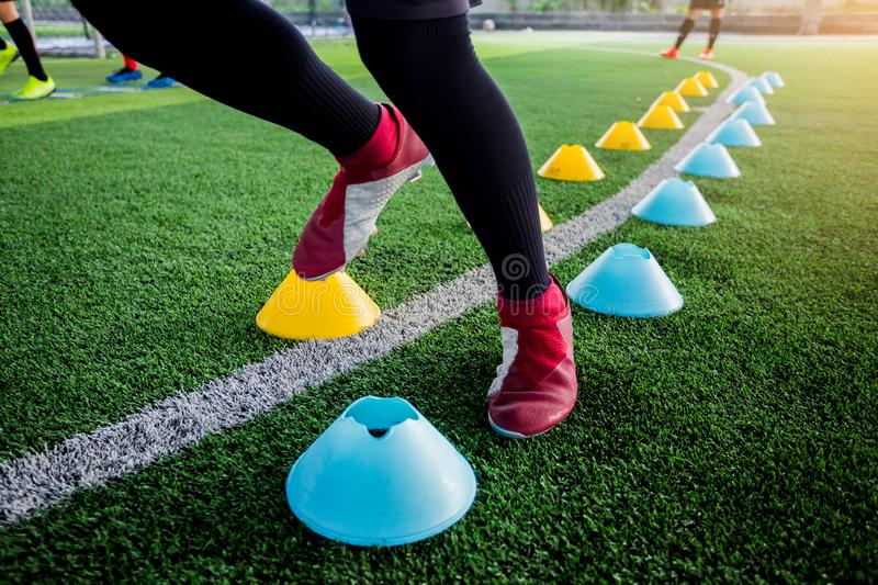 Soccer player Jogging and jump between cone markers on green art. Ificial turf for soccer training. Football or Soccer Academy stock photography