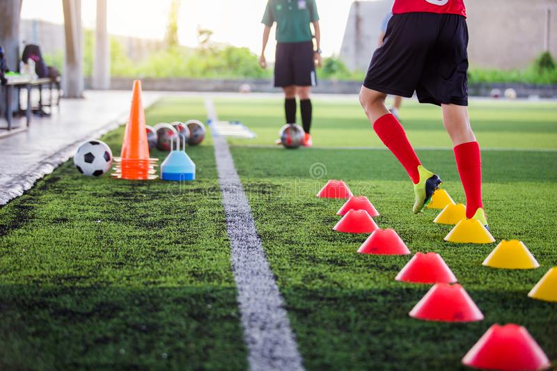 Soccer player Jogging and jump between cone markers on green artificial turf for soccer training. Football or Soccer Academy royalty free stock image