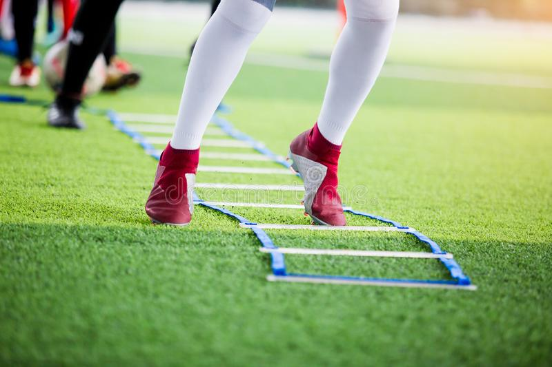 Soccer player jogging and jump between marker for football training with blurry other players waiting to follow him. Ladder drills exercises for football team royalty free stock image