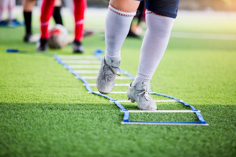 Soccer player jogging and jump between marker for football training with blurry other players waiting to follow him. Ladder drills exercises for football team stock photo