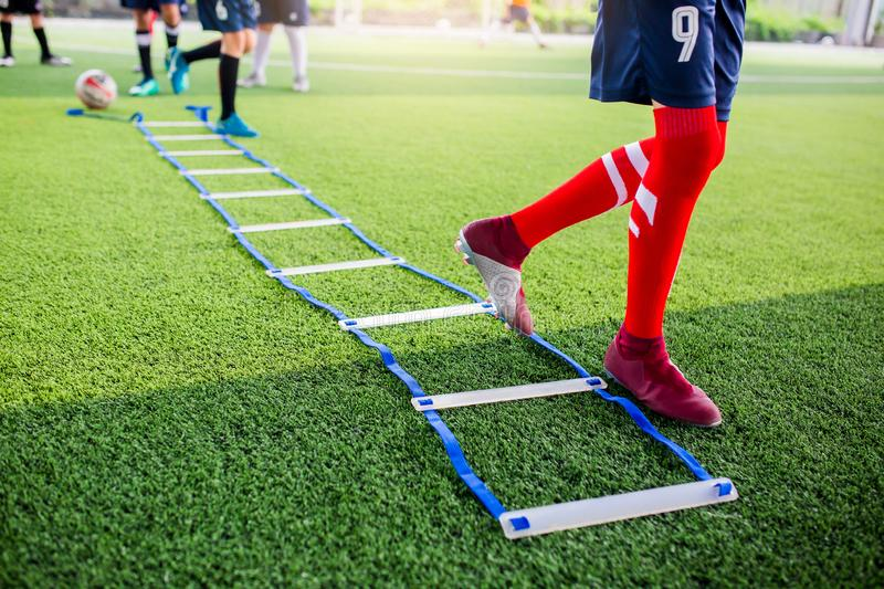 Soccer player jogging and jump between marker for football training with blurry other players waiting to follow him royalty free stock photography