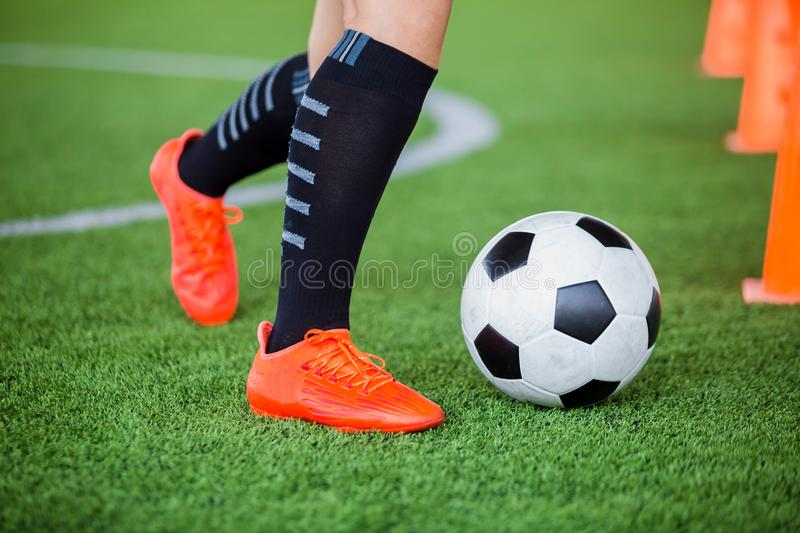 Soccer player jogging with trap and control football between cone markers. For football training royalty free stock photography