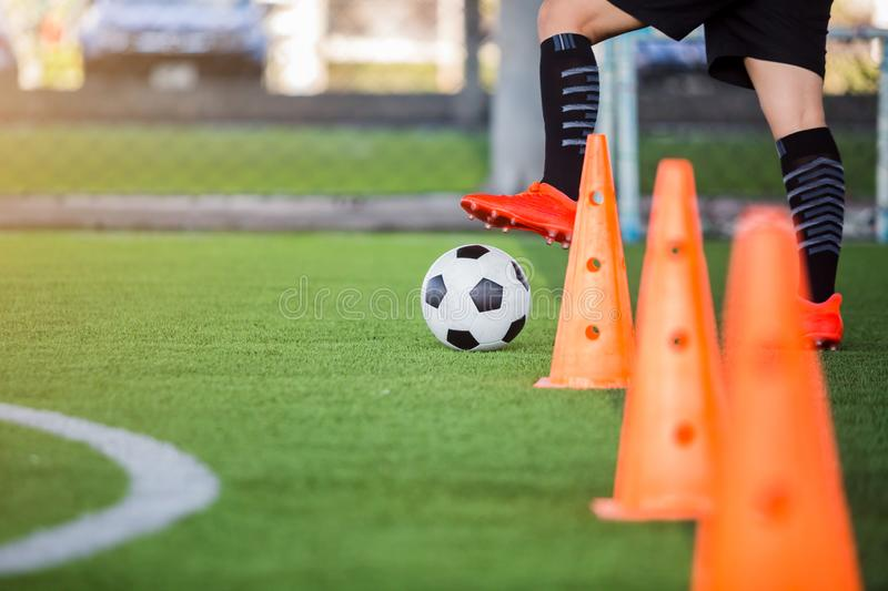 Soccer player jogging with trap and control football. Between cone markers for football training stock photo
