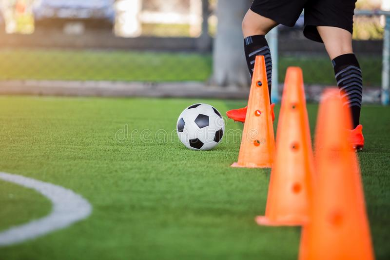 Soccer player jogging with trap and control football. Between cone markers for football training stock photography