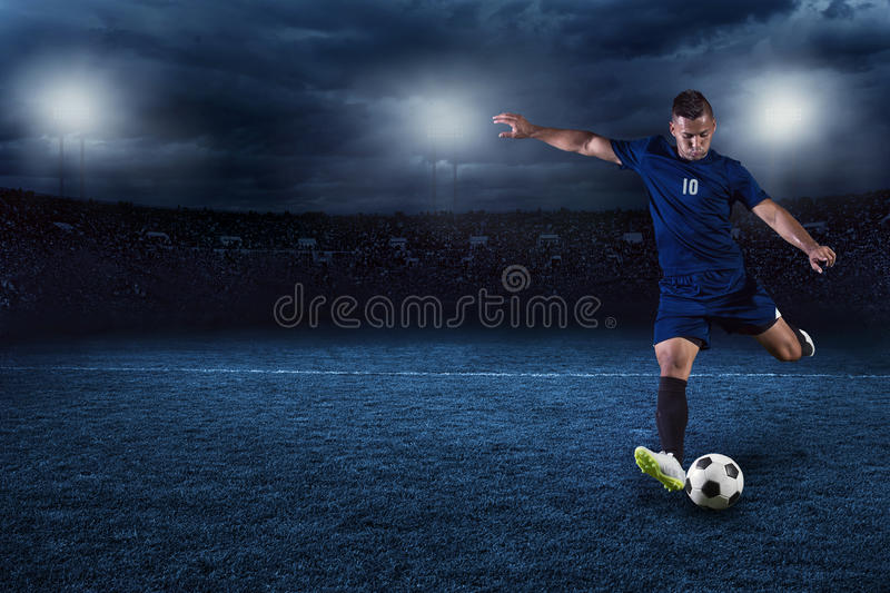 Soccer player kicking ball in a large stadium at night royalty free stock photography
