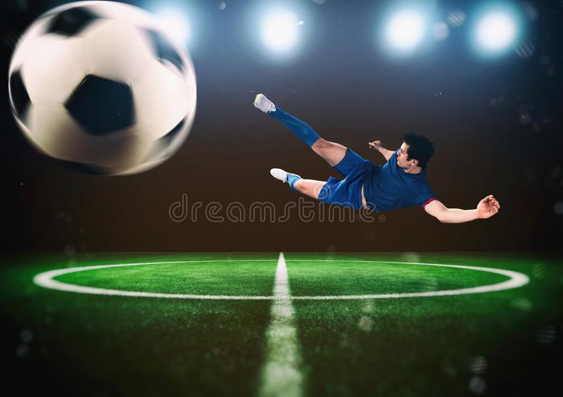 Football scene at night match with player kicking the ball with power royalty free stock image