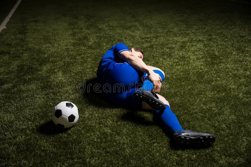 Footballer lying down with an injury stock photos