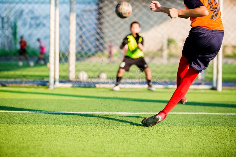 Soccer player run to shoot ball at penalty kick to goal with blurry goalkeeper background royalty free stock photography