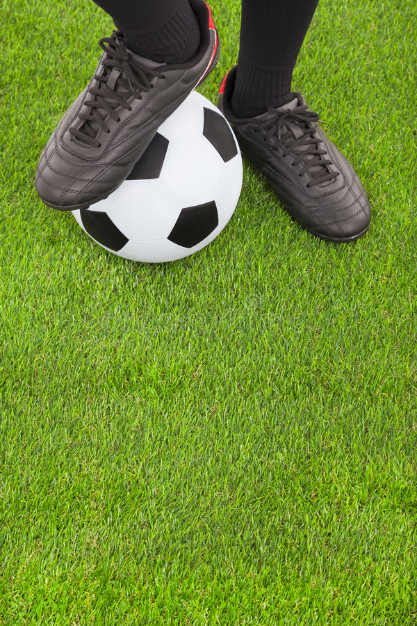 Soccer player's feet and football. On field royalty free stock images