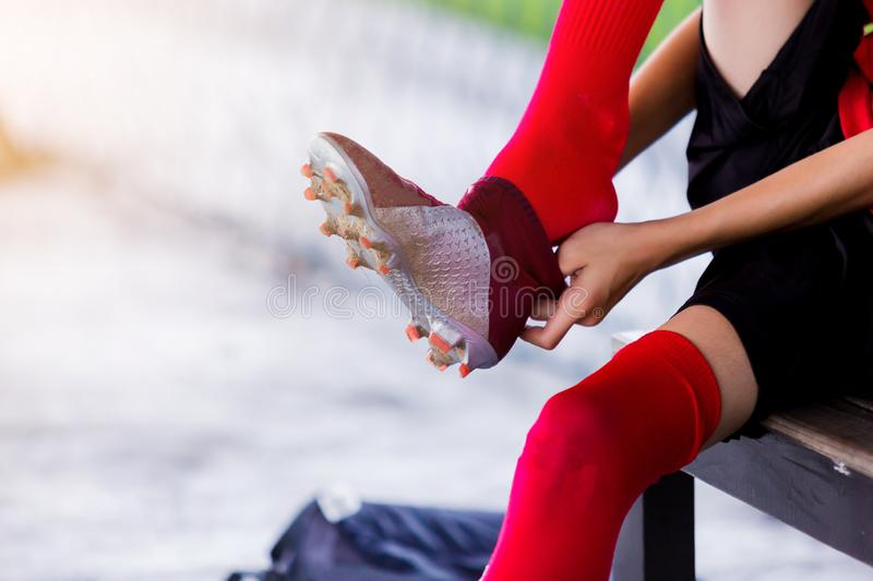 Soccer player is sitting and putting sport shoelaces. Soccer player is sitting and putting sport shoelaces before training football royalty free stock photo