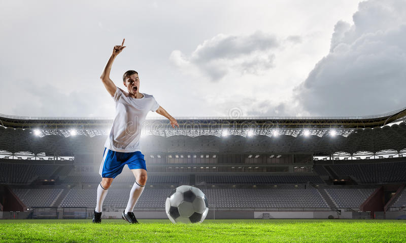 Soccer player at sport arena . Mixed media royalty free stock photo